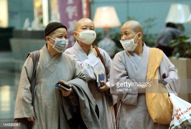 Three Buddhist nuns wear masks while walking at Chiang Kaishek International Airport at Taoyuan 10 April 2003 as scores of flights around the region...