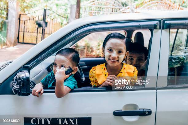 Three Burmese Children Smiling from the Drivers Seat of a Car