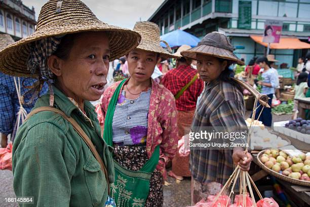 Three Burmese women discuss with potential clients the sale of their vegetables in the local market of Kyaukme, Shan State, Myanmar