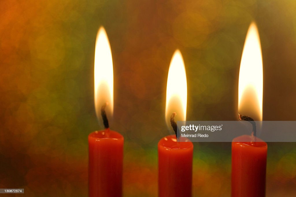 Three burning candles in front of a colourful background : Stock Photo