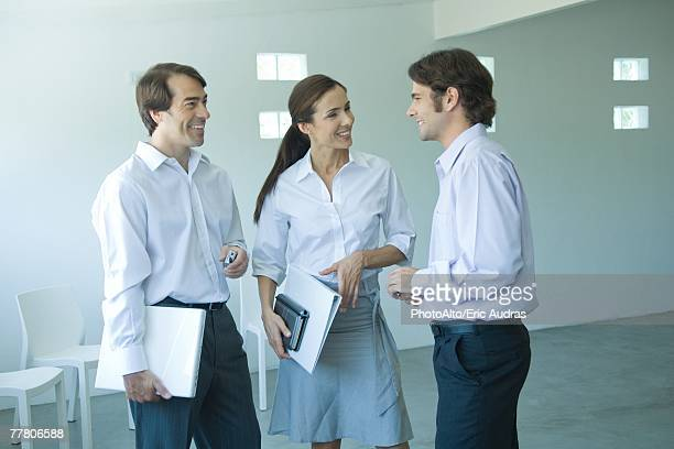 Three business associates chatting and smiling, three quarter length