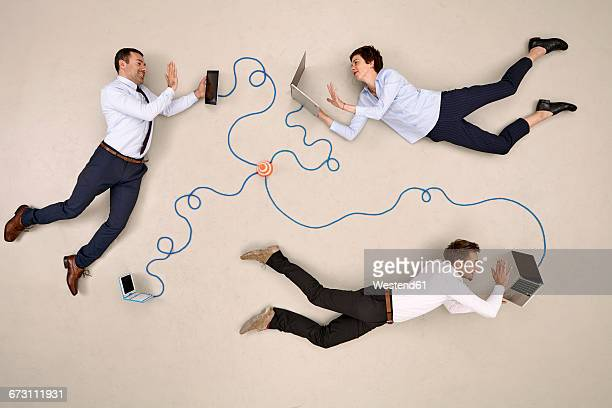 Three business colleagues being connected via devices, waving