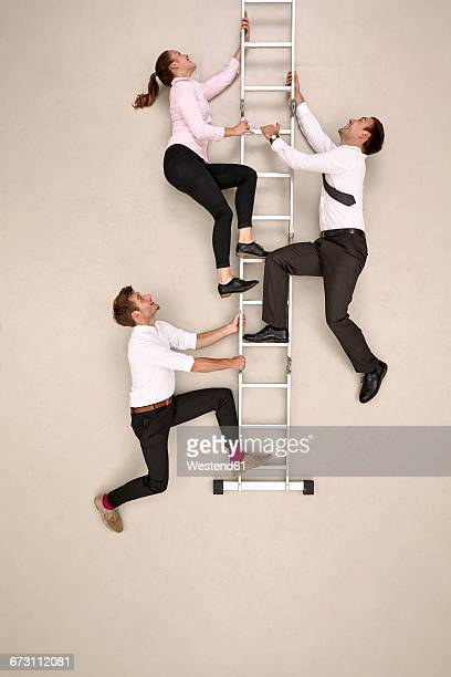 Three business colleagues climbing ladder