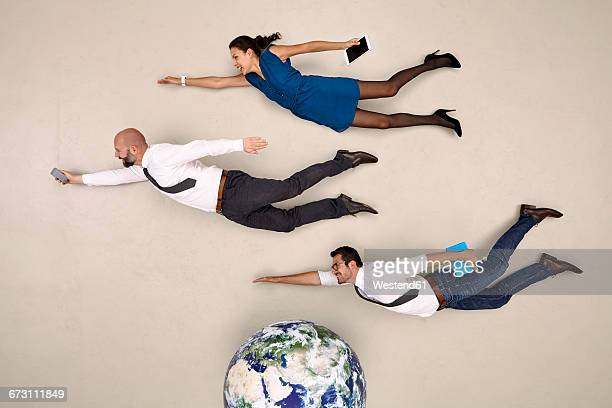 three business colleagues flying above the globe - flying stock photos and pictures