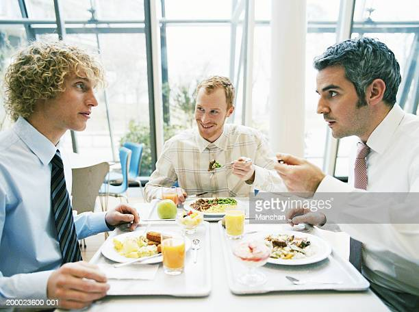 Three business colleagues in canteen having lunch, close-up