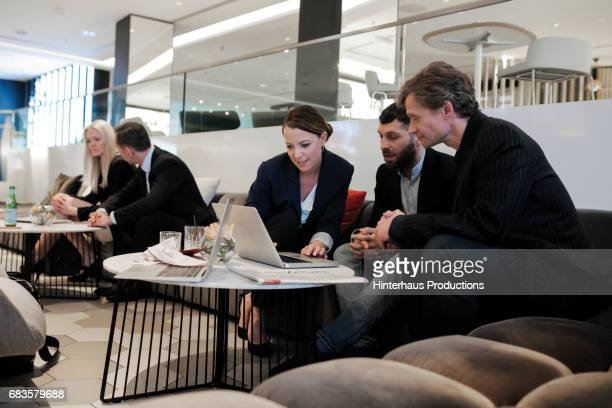 Three Business Colleagues Looking Over Their Work Schedule In A Hotel Lobby