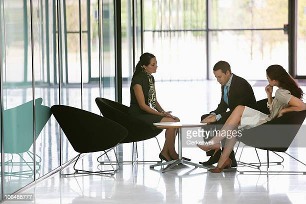 Three business executives having a meeting at office cafeteria