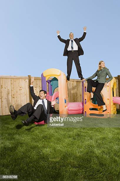 Three business executives having fun on a jungle gym
