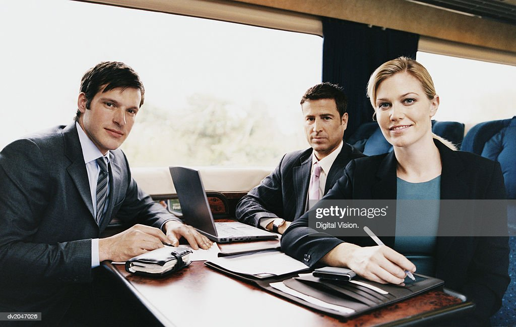 Three Business Executives Sitting at a Table on a Passenger Train : Stock Photo