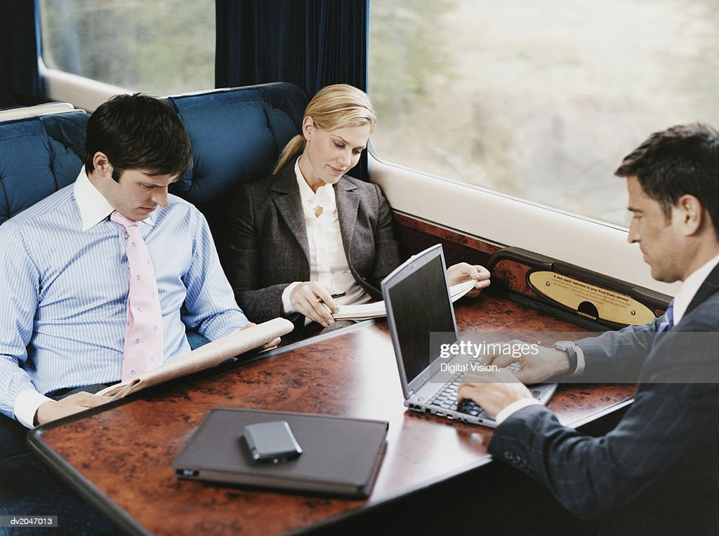 Three Business Executives Sitting on a Passenger Train : Stock Photo
