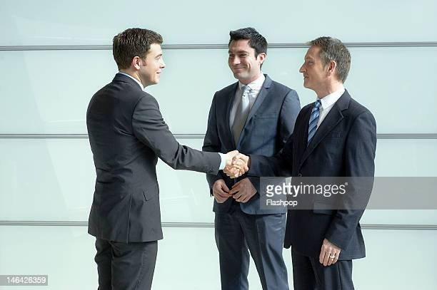 three business men having an informal meeting - handshake stock pictures, royalty-free photos & images