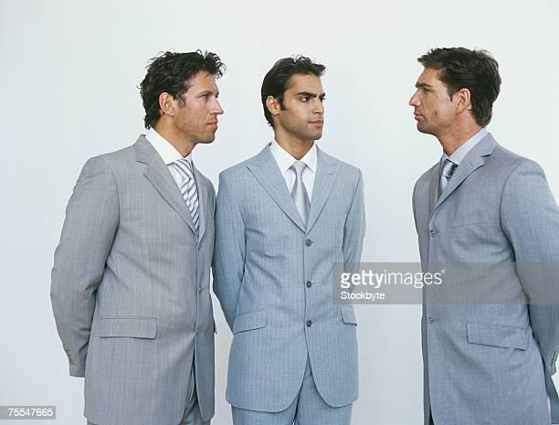 three business men in suits looking at each other,three quarter length - three quarter length stock-fotos und bilder