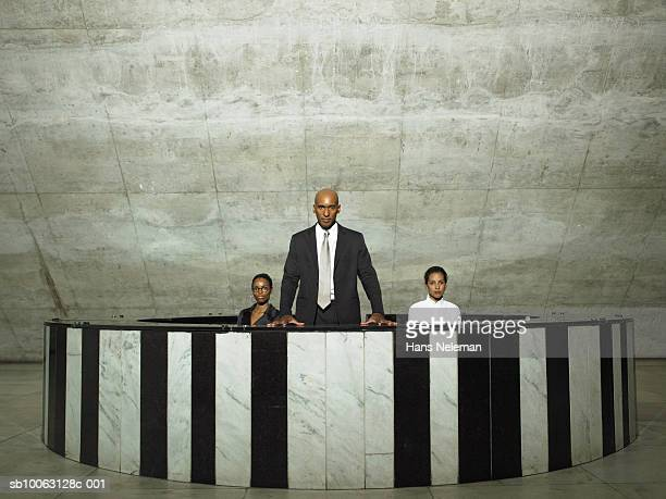 Three business people at reception desk, portrait