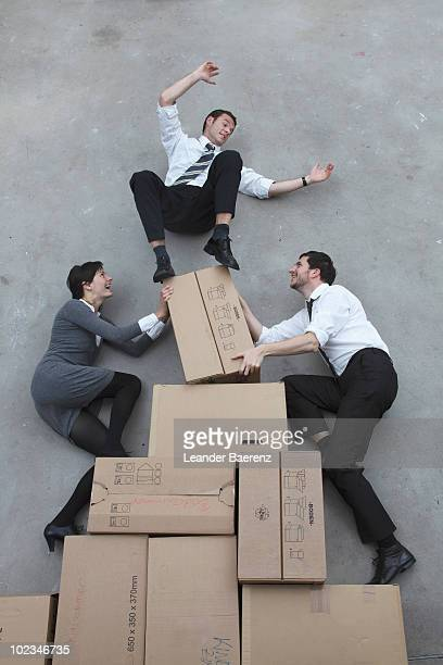 three business people balancing on cardboard boxes, smiling, portrait, elevated view - posizione descrittiva foto e immagini stock