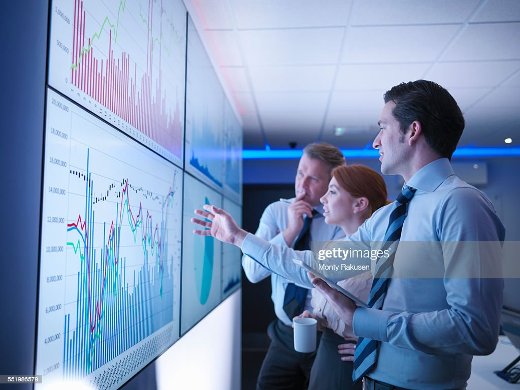 Three business people discuss graphs on screen in meeting room : Stock-Foto