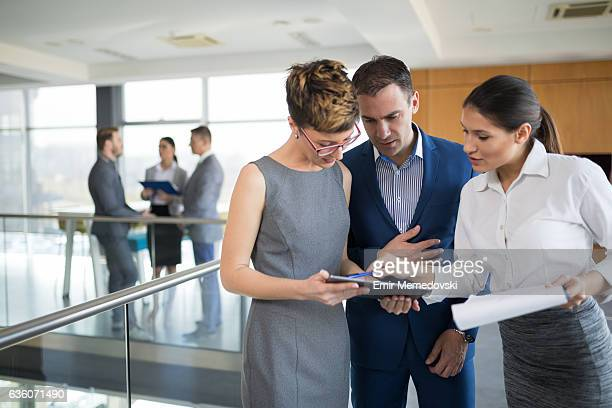 Three business people discussing business strategy using digital tablet