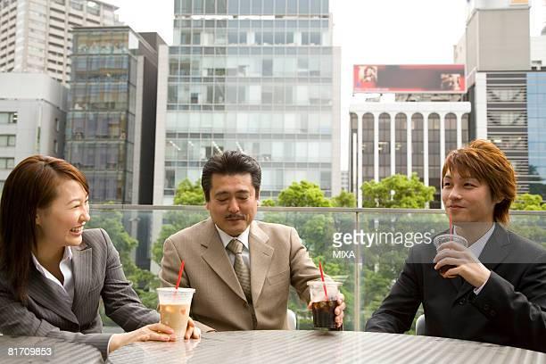 Three business people drinking coffee