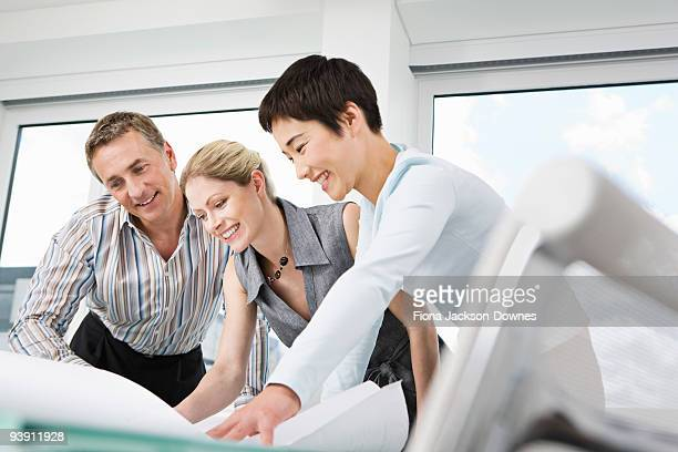 Three business people look at some plans