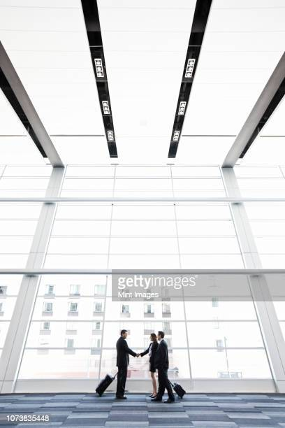 three business people meeting in front of a large window in a convention centre lobby. - building atrium stock pictures, royalty-free photos & images