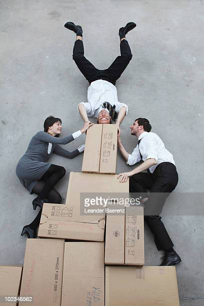 Businesspeople messing about on pile of boxes, man doing handstand