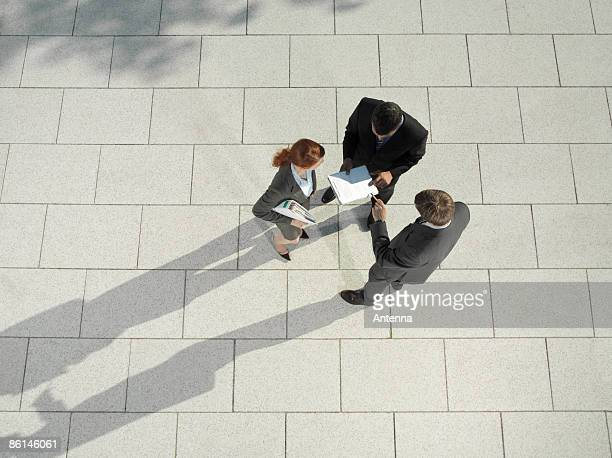 Three business people standing outside and discussing