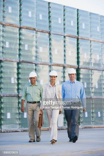 three business people walking on factory yard - pallet industrial equipment stock pictures, royalty-free photos & images