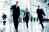 Three Business People Walking Quickly Though Office Entrance