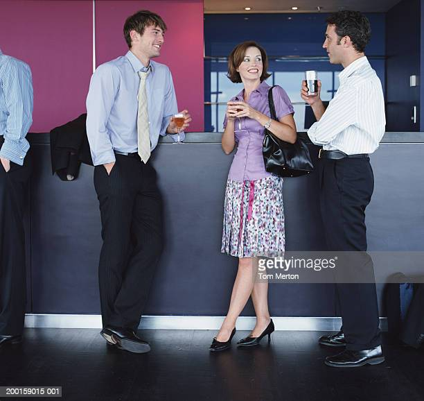 Three business people with drinks by bar counter