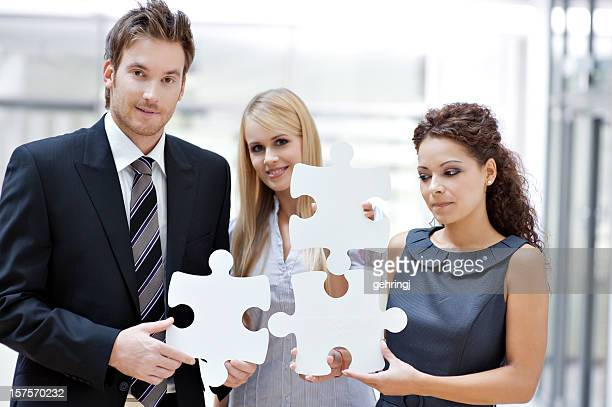 Three business people with puzzle