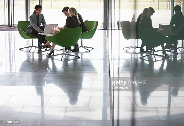 Three business people working at modern office cafeteria
