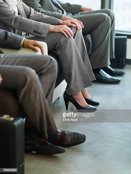 Three business people's legs in an office lobby