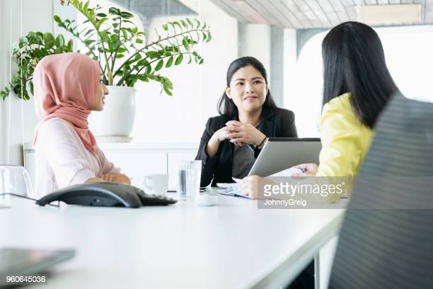 three business women discussing in meeting - malay hijab stock photos and pictures