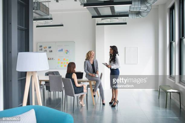 three business women happily talking in london office building - mid distance stock pictures, royalty-free photos & images