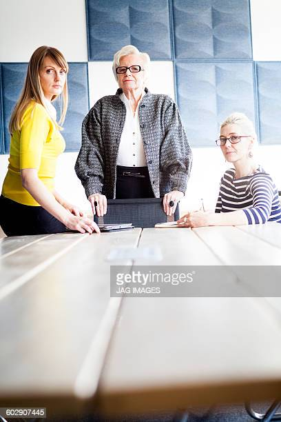 three business women of mixed ages look to camera
