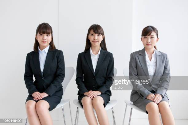 three business women sitting in a chair - formal businesswear stock pictures, royalty-free photos & images