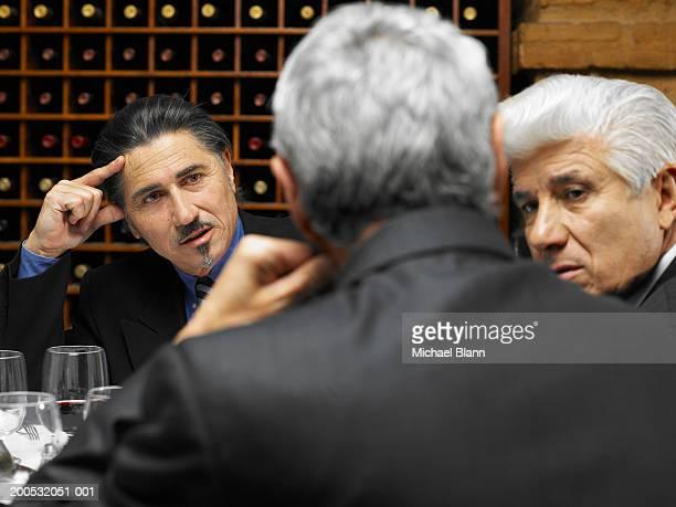 Three businessman having discussion in restaurant