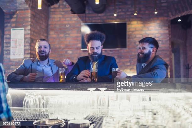 Tre affärsman ha kul efter arbete, sitter på baren counter