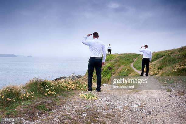 three businessman looking out over a clifftop