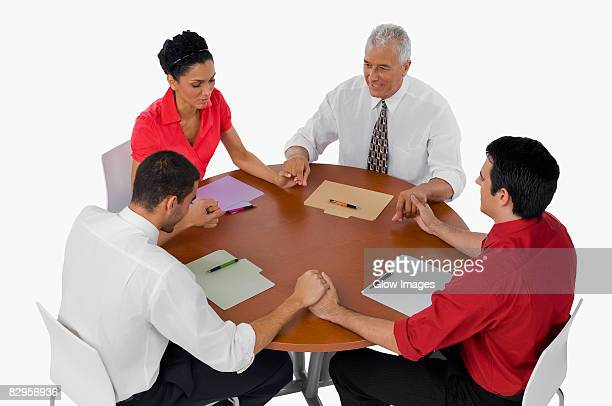 Three businessmen and a businesswoman praying with holding their hands in a meeting