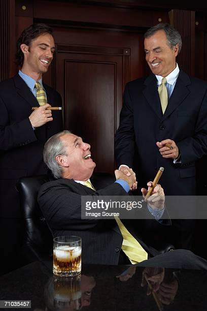 Three businessmen celebrating with cigars