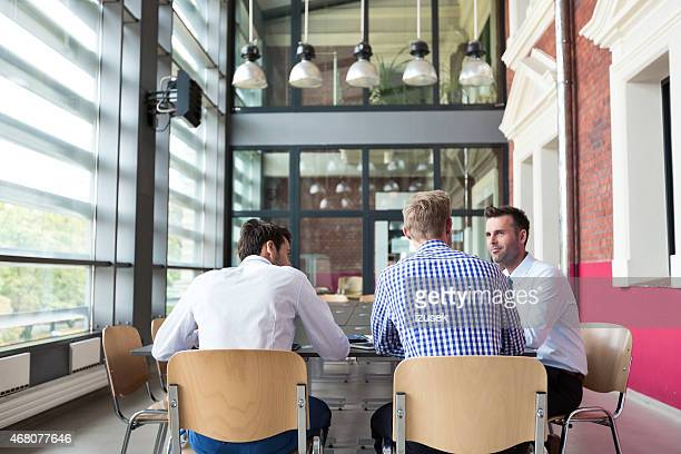 Three businessmen discussing in a meeting room