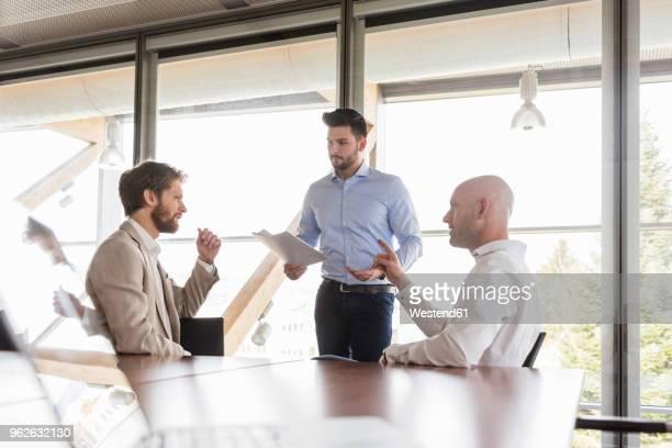 three businessmen discussing in conference room - geschäftsbesprechung stock-fotos und bilder
