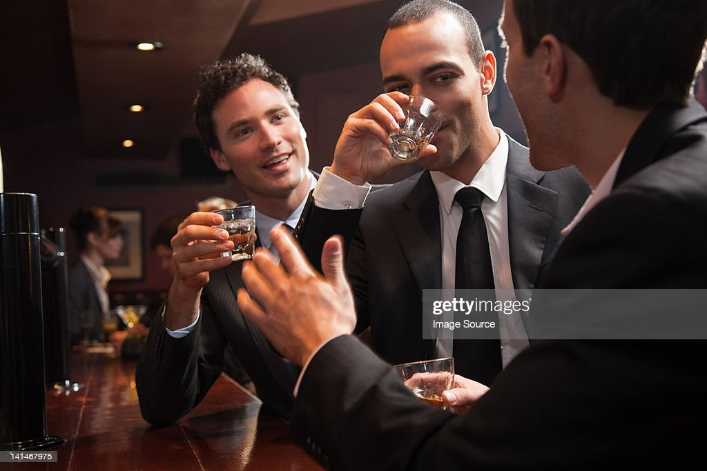 Three businessmen drinking at a bar : Foto de stock