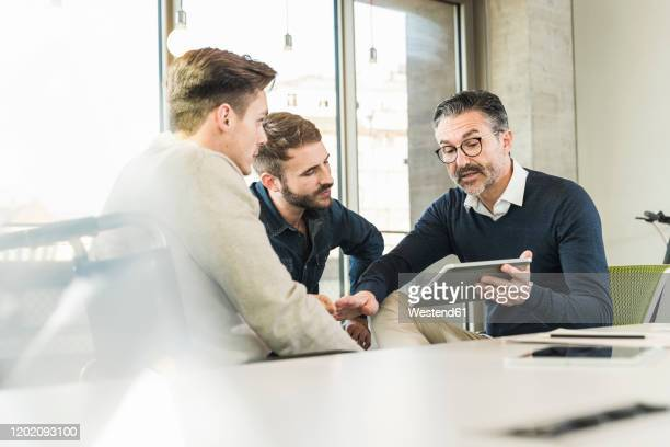 three businessmen having a meeting in office sharing a tablet - founder stock pictures, royalty-free photos & images