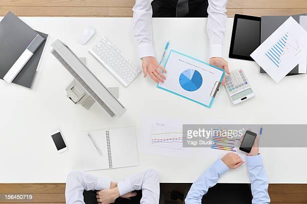 Three businessmen having discussion on desk