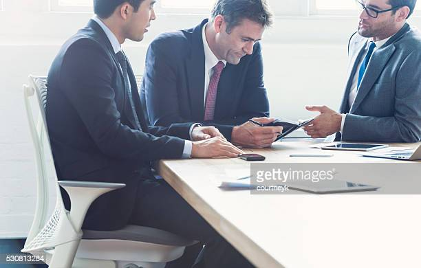 Three businessmen in a meeting.