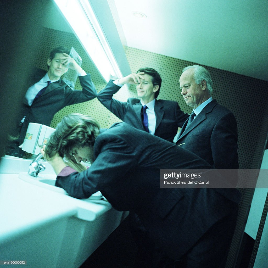 Three businessmen in bathroom, two with hands on head, side view. : Stockfoto