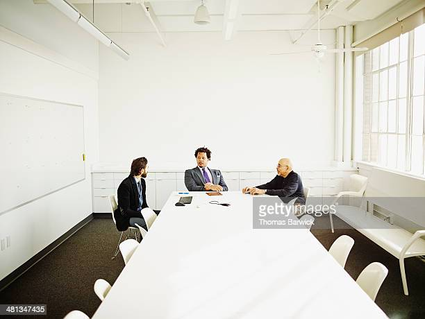 Three businessmen in discussion in conference room