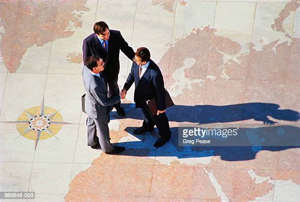 Three businessmen in discussion on world map, elevated view