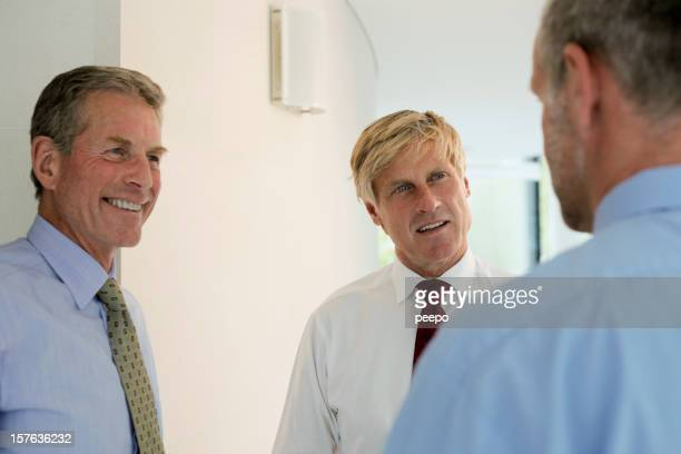 Three businessmen interacting with each other